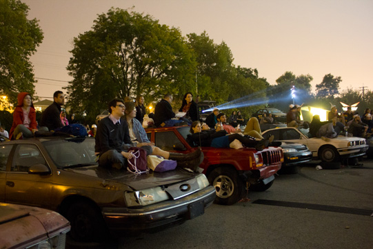 audience sitting on cars
